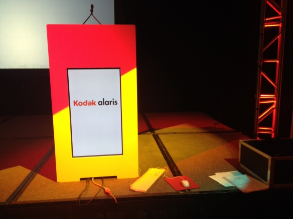 The setup crew puts finishing touches on the stage before Kodak Alaris' leaders start their dress rehearsals.