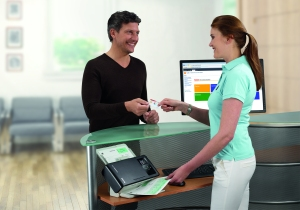 A customer service representative helps uses a Kodak ScanMate i1150 Scanner to quickly and easily capture customer information.